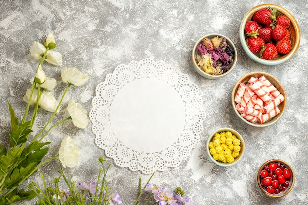 Bovenaanzicht verse rode aardbeien met snoepjes op witte oppervlakte fruit gelei bloemen