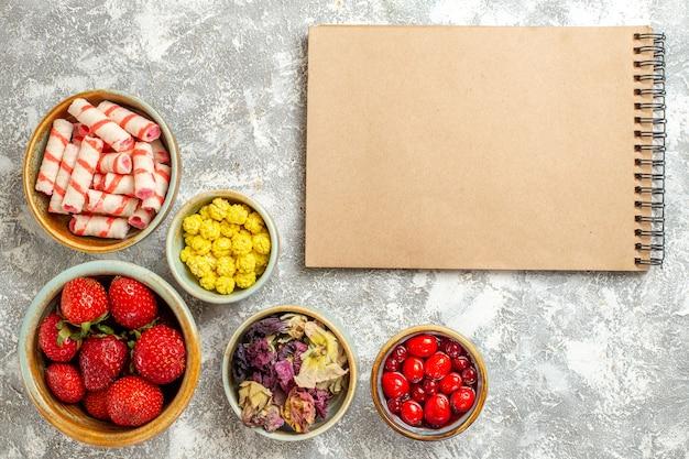 Bovenaanzicht verse rode aardbeien met snoepjes op witte oppervlakte fruit zoete snoep kleuren
