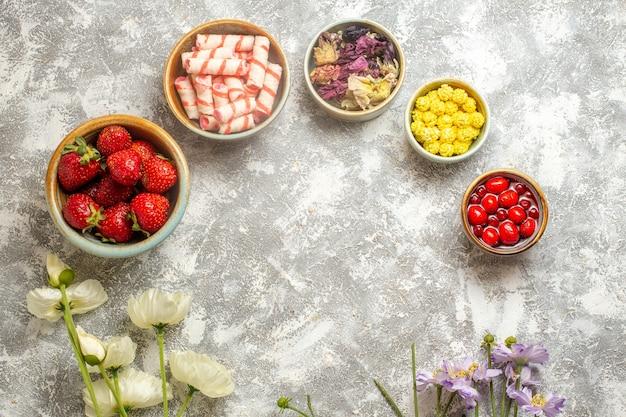 Bovenaanzicht verse rode aardbeien met snoepjes op witte oppervlakte kleur bessen fruit snoep