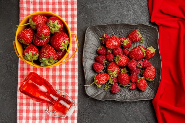 Bovenaanzicht verse rode aardbeien op de donkere tafel kleur fruit frambozen bes