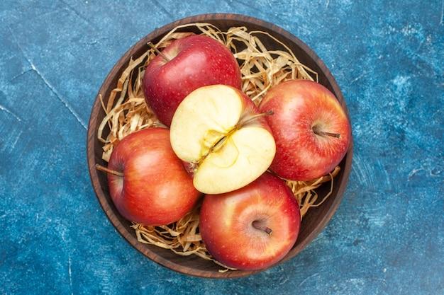 Bovenaanzicht verse rode appels binnen plaat op blauwe tafel