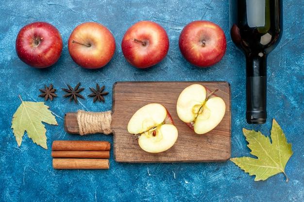 Bovenaanzicht verse rode appels met fles wijn op de blauwe tafel rijp fruit alcohol kleur foto boom