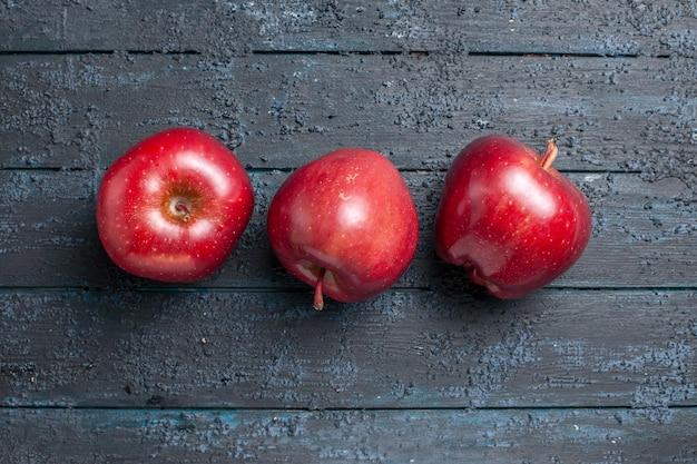 Bovenaanzicht verse rode appels rijp en zacht fruit op het donkerblauwe bureau veel fruitboom rode verse plantenkleur