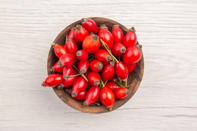 Bovenaanzicht verse rode bessen in kleine plaat op witte achtergrond
