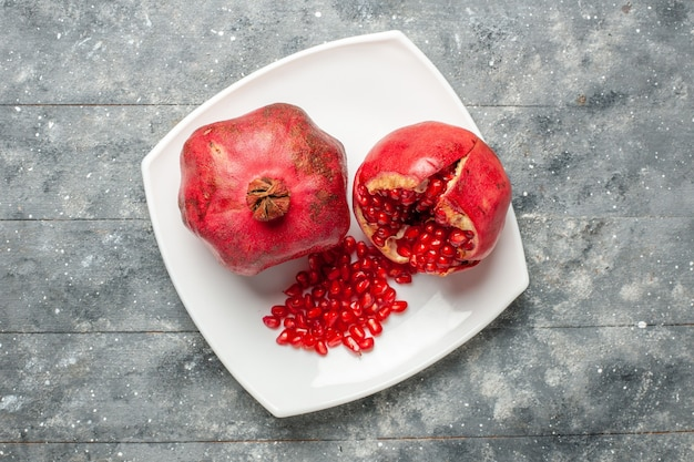 Bovenaanzicht verse rode granaatappels in plaat op grijs rustiek bureau