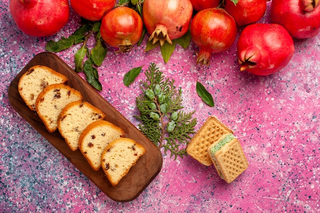 Bovenaanzicht verse rode granaatappels met gesneden cake en wafels op het roze oppervlak