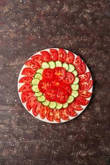Bovenaanzicht verse rode tomaten gesneden met komkommers verse salade op de bruine ruimte