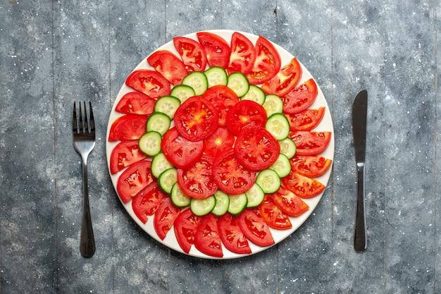 Bovenaanzicht verse rode tomaten gesneden verse salade op het grijze bureau