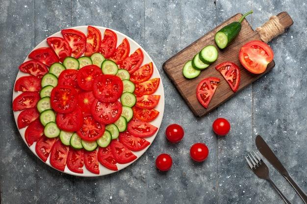 Bovenaanzicht verse rode tomaten gesneden verse salade op rustiek grijs bureau