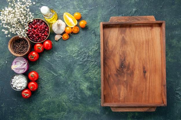 Bovenaanzicht verse rode tomaten met houten bureau op een donkerblauwe achtergrond gezondheid maaltijd salade voedsel kleur foto dieet vrije ruimte