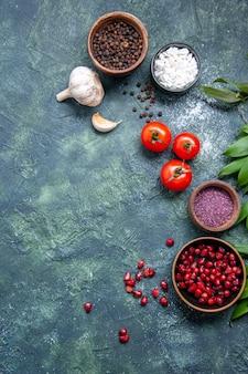 Bovenaanzicht verse rode tomaten met knoflook en kruiden op donkere achtergrondkleur rijpe salade maaltijd foto gezondheid dieet