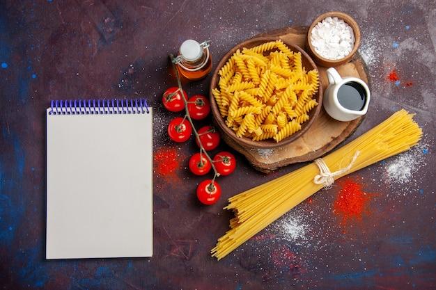 Bovenaanzicht verse rode tomaten met rauwe italiaanse pasta op het donkere bureau eten rauwe salade pasta maaltijd