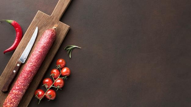 Bovenaanzicht verse salami met cherry tomaten