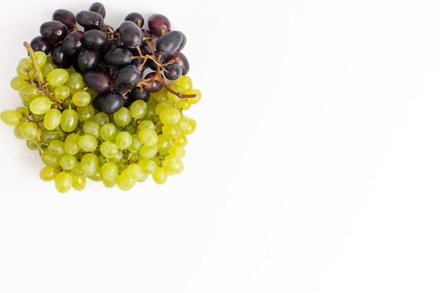 Bovenaanzicht verse, sappige druiven zacht op het witte bureau