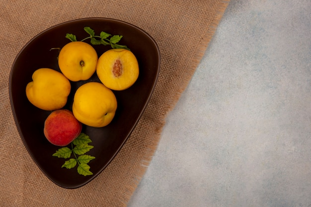 Bovenaanzicht verse sappige gele perziken op een kom op een zakdoek op een witte achtergrond met kopie ruimte