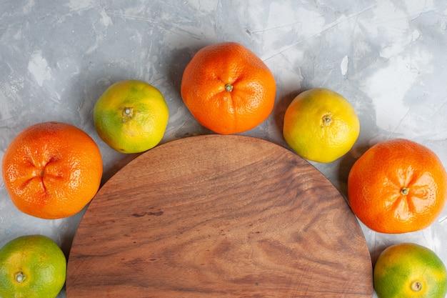 Bovenaanzicht verse, sappige mandarijnen, zachte citrusvruchten op het lichtwitte bureau citrusvruchten exotisch tropisch