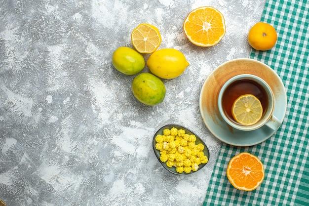 Bovenaanzicht verse schijfjes citroen met kopje thee op lichttafel