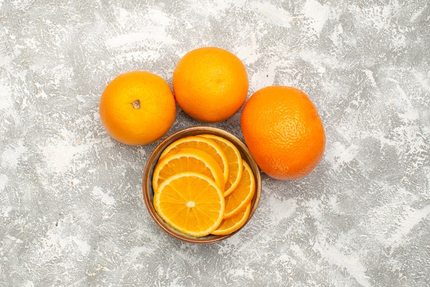 Bovenaanzicht verse sinaasappelen gesneden en hele zachte vruchten op de witte achtergrond citrus exotisch tropisch vruchtensap
