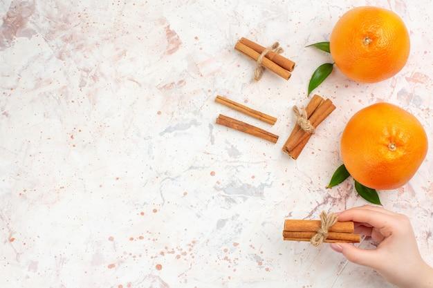 Bovenaanzicht verse sinaasappelen kaneelstokjes in vrouwelijke hand op helder oppervlak met kopie ruimte