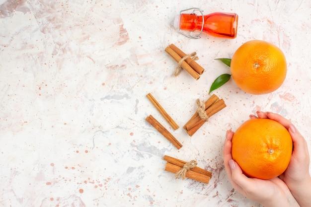 Bovenaanzicht verse sinaasappelen kaneelstokjes sinaasappel in vrouwelijke handfles op lichte oppervlak vrije plaats