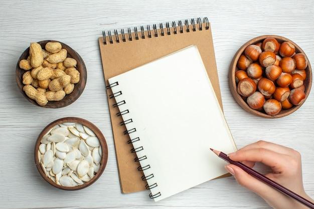 Bovenaanzicht verse smakelijke pinda's met witte zaden en hazelnoten op witte tafel