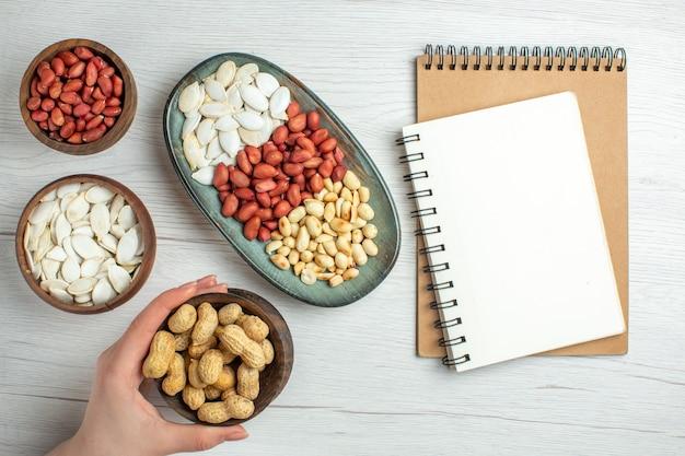 Bovenaanzicht verse smakelijke pinda's met witte zaden en notitieblok op witte tafel