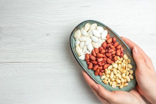 Bovenaanzicht verse smakelijke pinda's met witte zaden in plaat op witte tafel