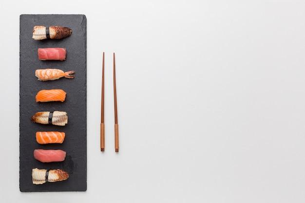 Bovenaanzicht verse sushi en eetstokjes met kopie ruimte