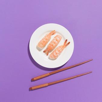 Bovenaanzicht verse sushi met stokjes op tafel