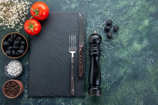 Bovenaanzicht verse tomaten met kruiden en olijven op donkere achtergrond