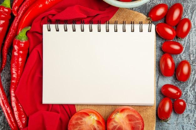 Bovenaanzicht verse tomaten met paprika en blocnote
