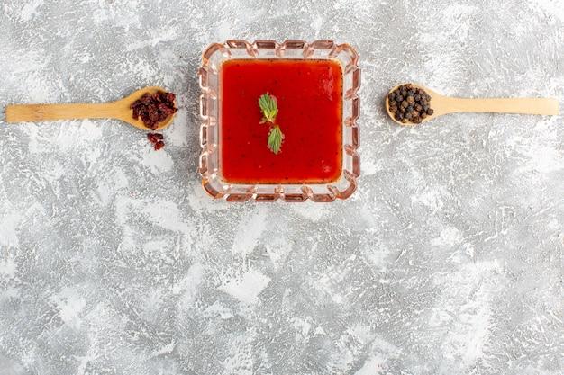 Bovenaanzicht verse tomatensaus binnen plaat op grijze tafel, soep eten maaltijd diner