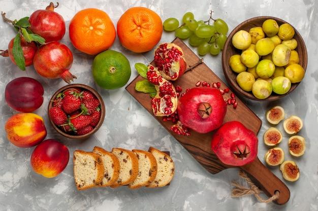 Bovenaanzicht verse vijgen met granaatappels, mandarijnen en druiven op wit bureau