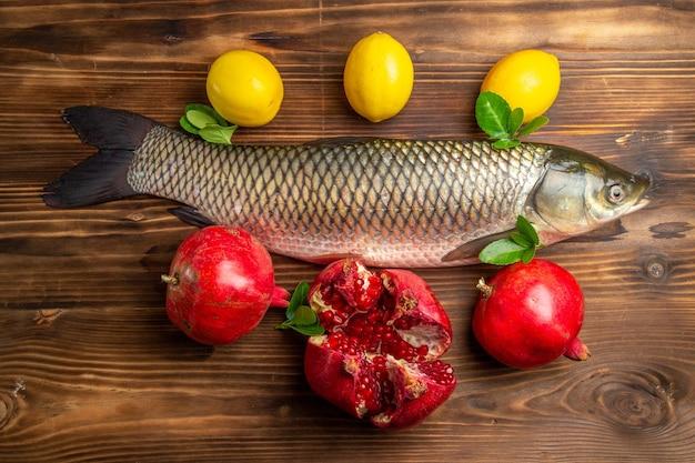 Bovenaanzicht verse vis met granaatappels en citroen op houten bureau