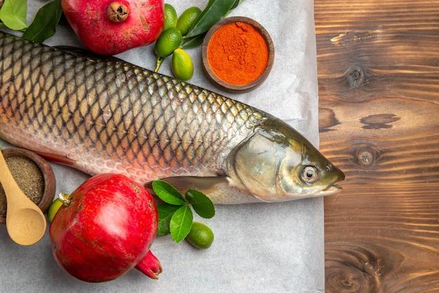 Bovenaanzicht verse vis met granaatappels op houten tafel eten zeevruchten schotel oceaan