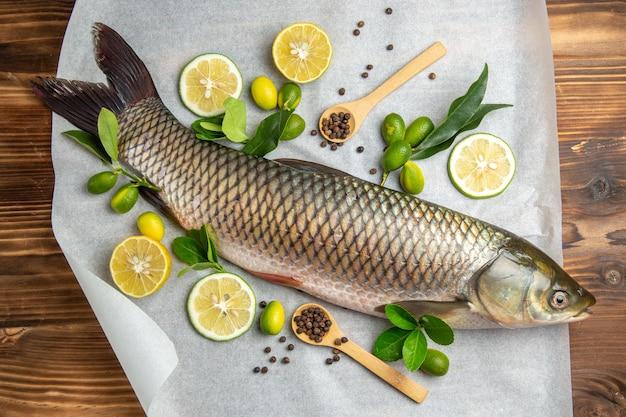 Bovenaanzicht verse vis met plakjes citroen op houten tafel voedsel zeevruchtenschotel oceaan