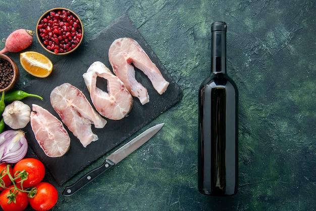 Bovenaanzicht verse vis plakjes met rode tomaten op donkerblauwe achtergrond oceaan vlees zeevruchten peper schotel voedsel zeemeel water wijn