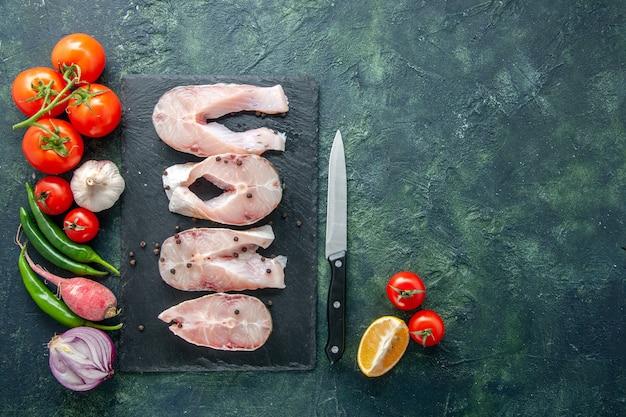 Bovenaanzicht verse vis plakjes met rode tomaten op donkere achtergrond oceaan vlees zeevruchten maaltijd water voedsel peper schotel