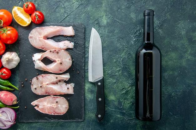 Bovenaanzicht verse vis plakjes met rode tomaten op donkere achtergrond oceaan vlees zeevruchten zeemeel water voedsel peper schotel wijn