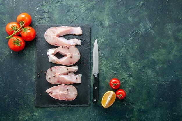 Bovenaanzicht verse vis plakjes met rode tomaten op donkere achtergrond oceaan vlees zeevruchten zeemeel water voedsel peper schotel