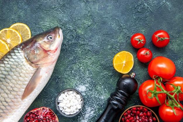 Bovenaanzicht verse vis, tomaten, pepermolen, schijfjes citroen op de keukentafel
