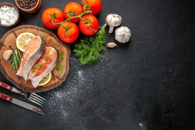 Bovenaanzicht verse visschijfjes met schijfjes citroen en tomaten op donkere tafel