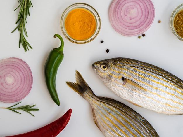 Bovenaanzicht verse vissen naast chili pepers