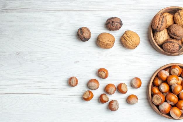 Bovenaanzicht verse walnoten met hazelnoten op witte tafel