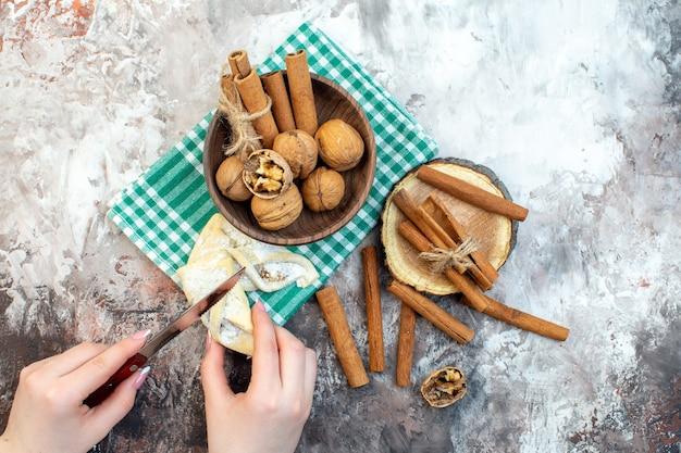 Bovenaanzicht verse walnoten met kaneel en vrouwelijke snijden gebak op lichte ondergrond