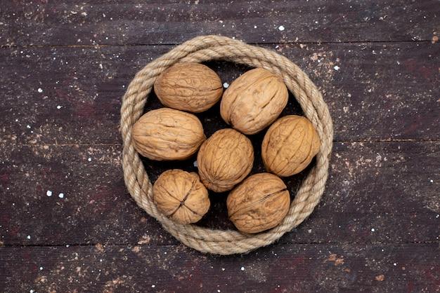 Bovenaanzicht verse walnoten met shell bekleed met touwen op bruin