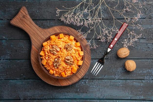 Bovenaanzicht verse wortelsalade geraspte salade met walnoten op donkere bureaudieetkleur notengezondheidssalade