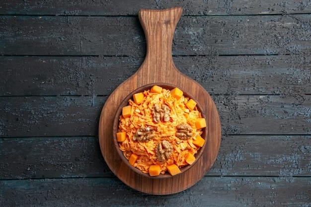 Bovenaanzicht verse wortelsalade geraspte salade met walnoten op het donkere bureau dieetsalade kleur noten gezondheid