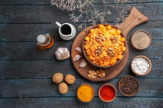 Bovenaanzicht verse wortelsalade met walnoten en kruiden op donkerblauwe bureaunoot dieetsalade kleur gezondheid