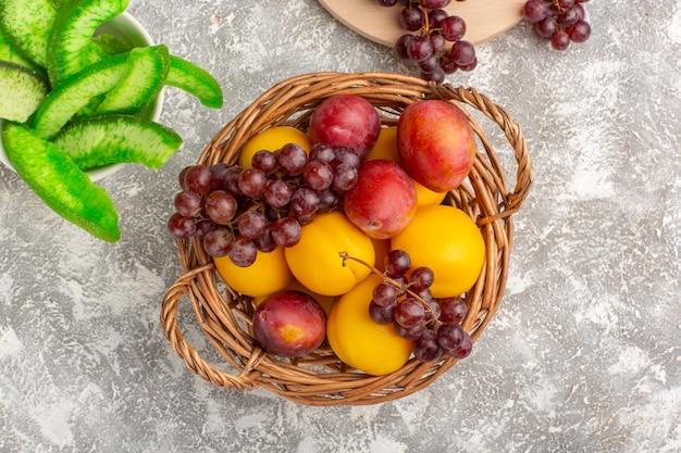 Bovenaanzicht verse zoete abrikozen met pruimen en druiven in mand op wit bureau